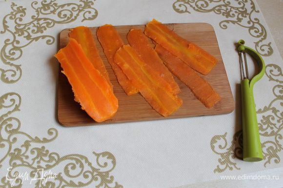 Морковь почистим и нарежем на плаcтинки овощечисткой. Лишнее нарежем на кубики.