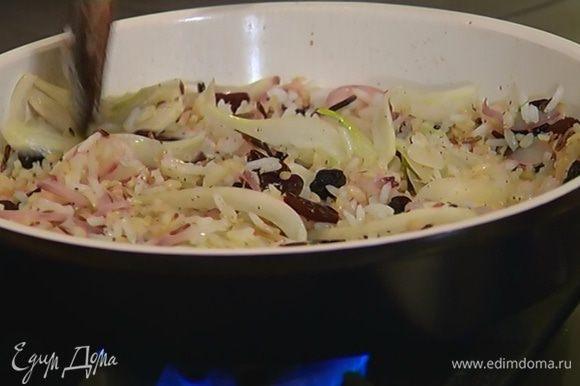 Добавить готовый рис, вишню и изюм, посолить, поперчить, перемешать и прогреть все на медленном огне.