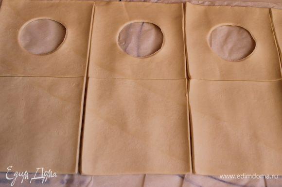 Развернем готовое слоеное тесто. Разрежем на квадраты 10 на 10 см, нам нужно парное число. В половине квадратов вырежем рюмкой серединку.