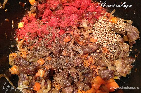 Когда лук станет прозрачным, добавить в казан морковь и перемешать. Обжаривать в течении нескольких минут помешивая. Затем посолить, поперчить, добавить по чайной ложке зиры , кориандра, паприки, острого перца на кончике ножа и снова перемешать.