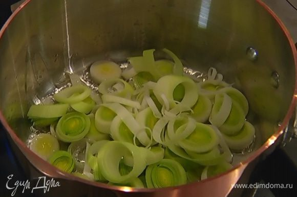 Разогреть в кастрюле оливковое масло и обжарить порей до прозрачности.