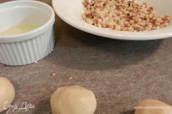 Сформировать шарики (2 ч.л. на каждый). Макать шарики поочередно сначала в взбитый вилкой белок, потом опускать в измельченные орехи.