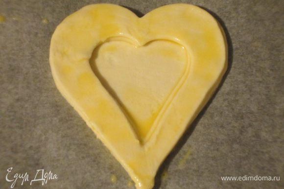 На каждое такое сердечко выложить по 2 полых, смазывая края яйцом. Дно волованов наколоть вилкой. Выпекать в разогретой до 200 °С духовке 10 минут. Остудит на решётке.