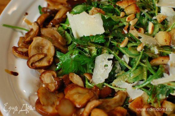 Выложить на блюдо часть листьев руколы, посыпать орехами и сухариками, затем выложить оставшуюся руколу, снова посыпать орехами и сухарями. По краям салата разложить горячие обжаренные грибы, сбрызнуть бальзамическим уксусом, посыпать хлопьями пармезана.
