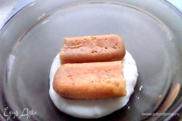 Быстро обмакнуть печенье в остывший кофе и положить сверху крема.