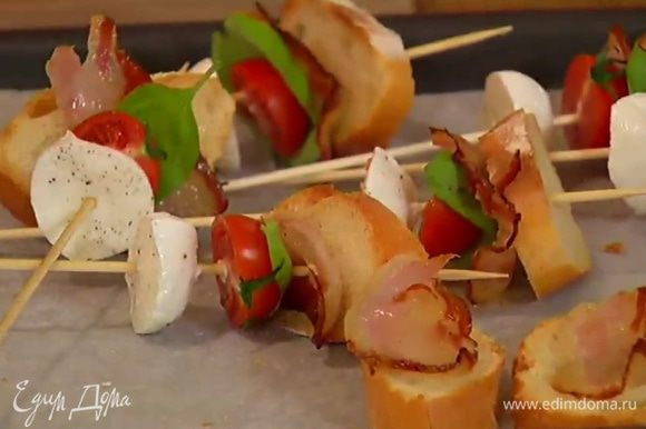 На каждую деревянную шпажку нанизать кусочек моцареллы, половинку помидора, лист базилика и кусочек хлеба с салом.