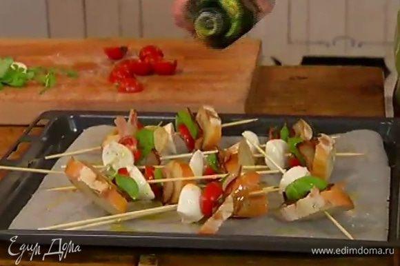 Сбрызнуть овощи и хлеб на шпажках оливковым маслом и отправить под гриль на 2–3 минуты.