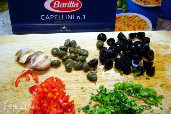Т.к. процесс приготовления пойдет быстро, приготовим все ингредиенты: чеснок раздавим прямо в кожуре, оливки и перец чили порежем, нарежем стебли петрушки. Поставим кипятиться воду для спагетти.
