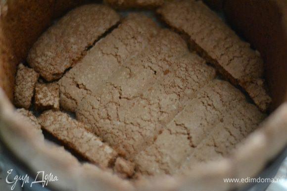 Достать из холодильника форму с савоярди и выложить плотно друг к другу низ бисквитным шоколадным печеньем. Пропитать его совсем слегка,