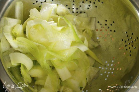 Цукини очистить от кожицы. С помощью овощечистки нарезать кабачок тонкими полосками-лентами. Положить в дуршлаг, посолить, перемешать и дать постоять около 10 минут.