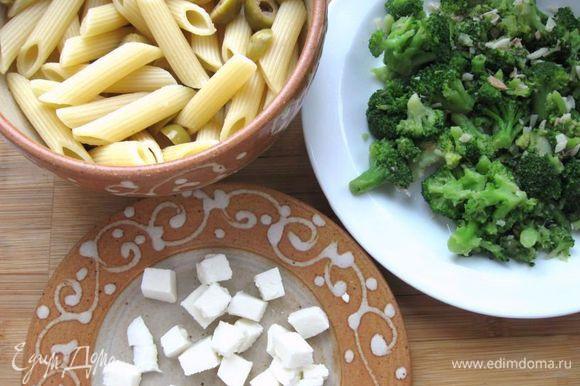 На раскаленную сковороду с оливковым маслом выложить порезанное филе анчоусов и чеснок, подержать 1 минуту, помешивая. Положить капусту в кастрюлю с подсоленной кипящей водой и варить 1 минуту. Достать брокколи из воды, откинуть на дуршлаг и добавить к анчоусам на сковороду. Тушить на сковороде примерно 1 минуту (если взять свежую капусту брокколи, время надо увеличить до 5 – 6 минут). Снять с огня, посолить, поперчить, дать остыть. Моцареллу нарезать кубиками, соединить пасту с капустой, моцареллой, оливками, перемешать.
