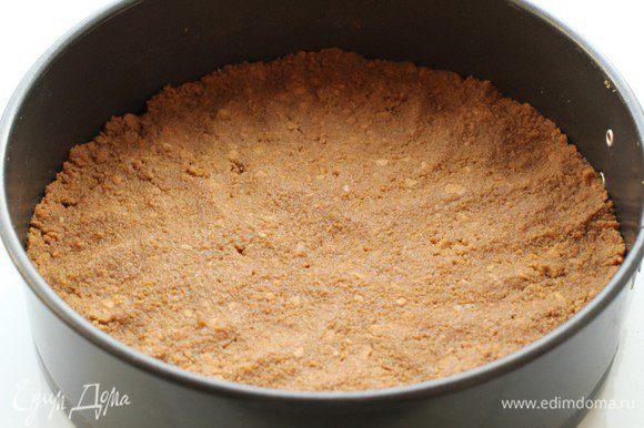 Соединить крошку с размягченным сливочным маслом, хорошо перемешать и выложить в застеленную пергаментом форму. Утрамбовать. Убрать в холодильник до тех пор, пока будет готовиться начинка.