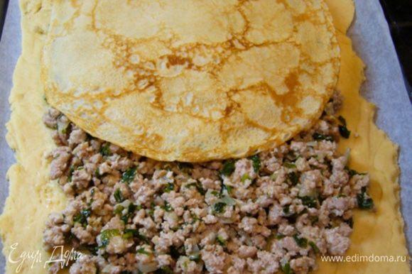 Выложить на тесто мясную начинку, оставляя поля. Проложить блинами.