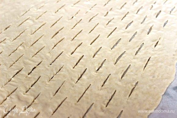 Оставшуюся часть теста немного раскатать, сделать острым ножом параллельные надрезы в шахматном порядке (каждый длиной по 2 см.).