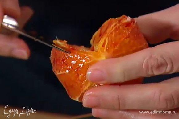 С апельсина срезать кожуру и вырезать мякоть из перепонок, сохранив выделившийся при этом сок.
