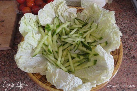 Листья капусты выложить на блюдо. Огурцы нарезать соломкой и выложить сверху.