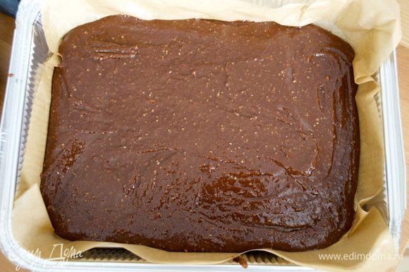 Прямоугольную форму (23 Х 30 см) застелить пекарской бумагой и выложить полученную шоколадную смесь. Разровнять лопаткой. Толщина слоя должна получиться примерно 1 см.