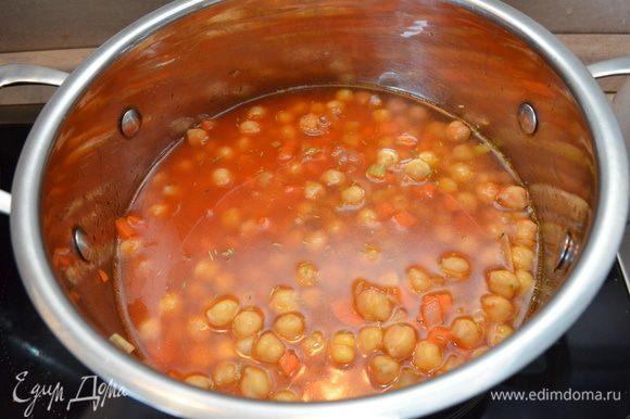 Добавляем томатную пасту, нут (пару ложек нута отложить для подачи) и горячий бульон. Варим 10-15 минут. Солим, перчим по вкусу. Я делала из отварного нута, в сухом виде около 200 г.