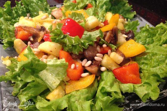 На листья салата выложите овощи, посолите, поперчите по вкусу, сверху посыпьте кедровыми орешками.