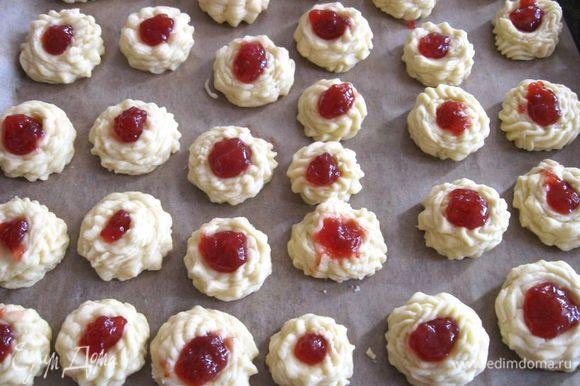 Мокрым пальцем сделать в каждом печенье углубление и положить туда джем, в который добавлен крахмал (чтобы не растекалась начинка) в пропорции 10: 1. Выпекать печенье при 200 градусах 20 минут. Минут через 15 проверить печенье, вам может потребоваться немного меньше времени.