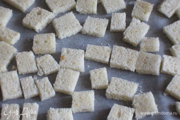У хлеба обрезать корку и нарезать кубиками.Выложить на противень с пергаментом и подсушить в разогретой до 180 °С духовке до золотистого цвета.