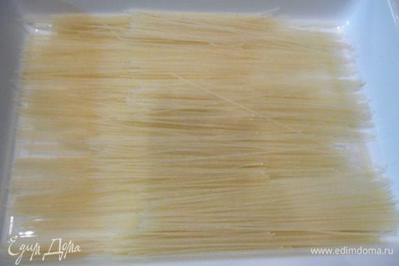В емкость для запекания выложить рисовую лапшу, залить ее кипятком.