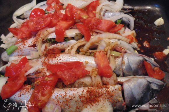 На скумбрию сверху выложить оставшийся лук, чеснок, помидор. Полить соевым соусом, посыпать паприкой. Оставить мариноваться на 2 часа, через 1 час рыбу перевернуть.