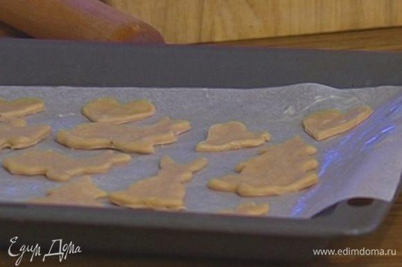 Противень выстелить бумагой для выпечки, смазать ее оставшимся сливочным маслом и выложить пряники.