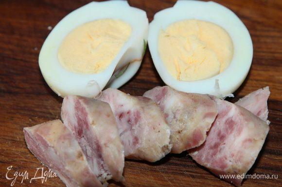 На каждую порцию нарезаем домашние колбаски и кладем по половинке вареного яйца.