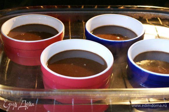 Разлить полученную смесь по креманкам, приблизительно 125 мл в каждую... Поставить креманки в глубокую форму с высокими бортами и осторожно наполнить форму горячей водой, на 2/3 высоты формочек. Поставить в духовку. Запекать от 40 минут до 1 часа (зависит от Вашей духовки). Формочки с готовым крем-брюле остудить и поставить в холодильник.