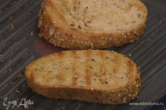 Разогреть в сковороде-гриль оливковое масло и обжарить хлеб с двух сторон.
