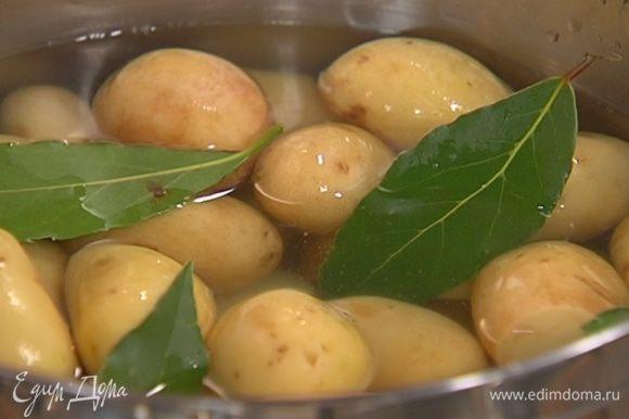 Выложить картофель в кастрюлю, добавить лавровые листья, залить кипятком и варить без добавления соли 7–10 минут до полуготовности, затем воду слить и вынуть лавровые листья.