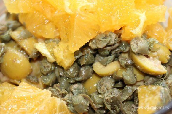 Для начала приготовим заправку. Апельсин очистить и порезать кубиком, добавить разрезанные оливки, каперсы и сушеный тимьян.