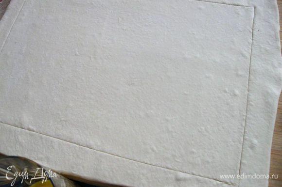 Тесто вынуть из морозильной камеры, разморозить, раскатать по размеру прямоугольной формы с низкими бортами (у меня форма 24 Х 32), острым ножом по периметру на расстоянии 2,5 – 3 см сделать разрез не на всю глубину слоя теста, чтобы бортики теста во время выпечки могли подняться. Форму застелить бумагой для выпечки, положить тесто.