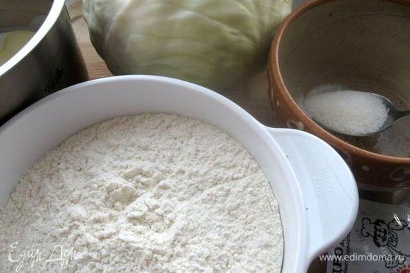 Приготовить муку, капусту и другие ингредиенты. Вылить смесь растительного масла и кефира в большую кастрюлю, где нужно замесить тесто. Добавить сахарный песок и соль, перемешать. Смешать сухие дрожжи с мукой и добавить в теплую смесь.