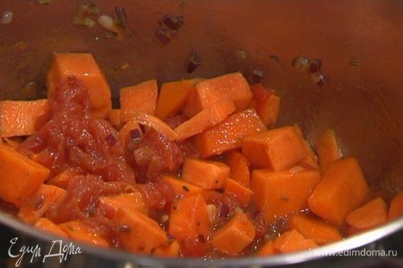 Выложить в кастрюлю с луком батат и тыкву, перемешать, добавить помидоры в собственном соку и еще раз все перемешать.