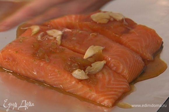 Противень выстелить фольгой, выложить замаринованную рыбу и полить оставшимся маринадом.