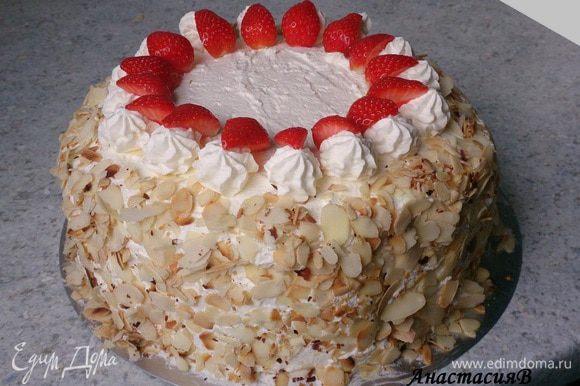 500 мл сливок крепко взбить с загустителем, 75 г сахара и 1 пакетиком ванильного сахара. 1/4 крема наполнить кондитерский мешок со звездообразной насадкой. Другой частью крема обмазать весь торт. Затем по бокам обсыпать миндалем. Украсить торт сливками и оставшейся клубникой.