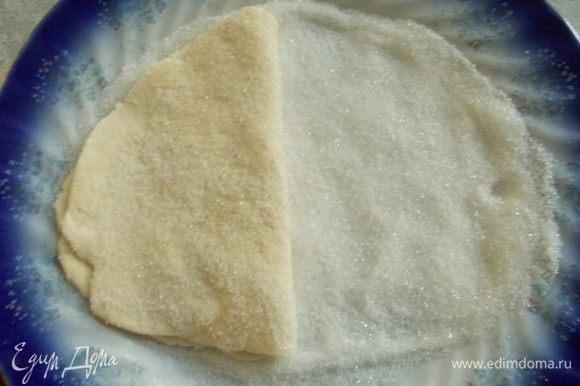 Переворачиваем тесто и опять вдавливаем в сахар. Затем складываем тесто пополам.