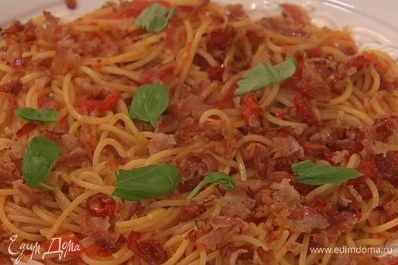 Спагетти с соусом выложить в большую тарелку, посыпать измельченным беконом и листьями базилика.