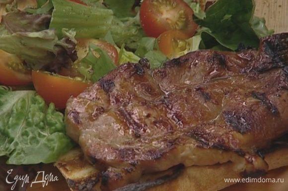 Положить на одну половину несколько разрезанных помидоров, горсть листьев салата и кусок мяса. Поперчить и накрыть другой половиной хлеба.