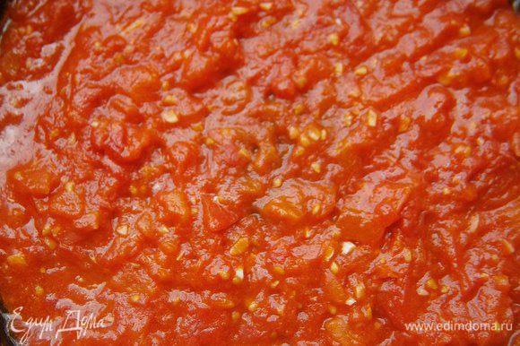 В сковороде раскалить 2 ст. л. растительного масла, добавить нарезанные помидоры, чеснок и готовить, помешивая, 2 - 3 минуты.
