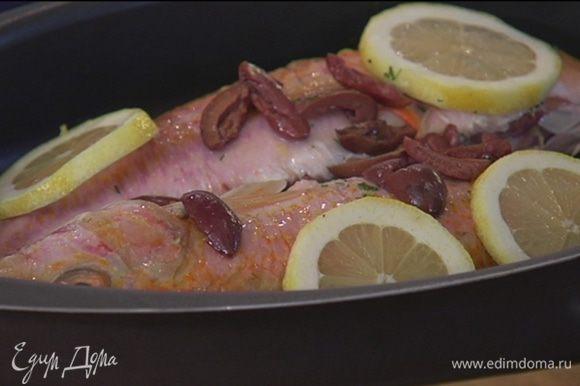 Рыбу выложить в противень, посыпать оливками, полить лимонным соком, сверху на рыбу выложить кружки лимона.