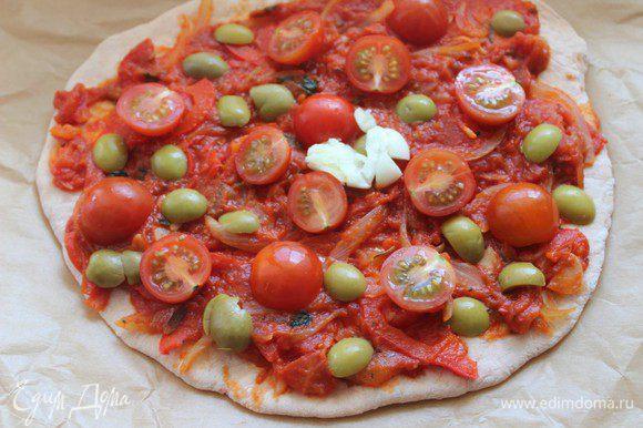 В центр каждой лепешки положить по зубчику раздавленного чеснока. Вокруг разложить половинки помидор черри и оливки.