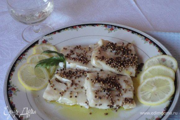 Закрыть крышкой или пищевой фольгой. Запекать при температуре 190 градусов в течение 15 минут. Лимонный сок смешать с двумя столовыми ложками оливкового масла. При подаче горячую рыбу сбрызнуть лимонным соусом.