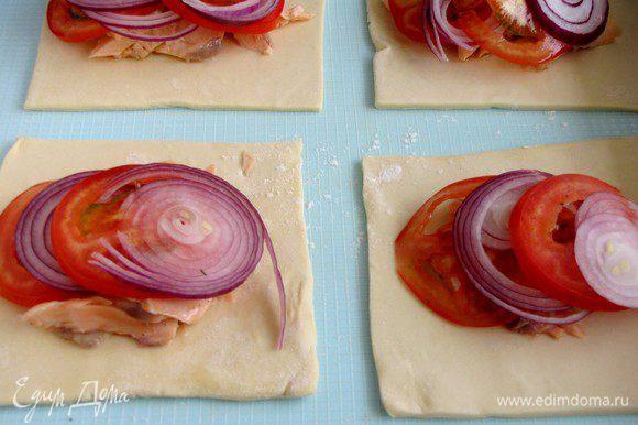 Сверху на рыбу выложить лук и помидоры.