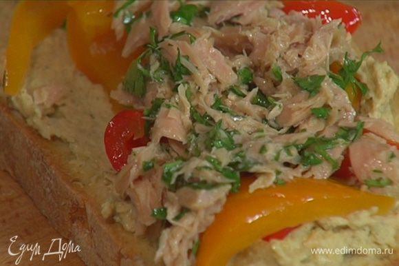 Кусок хлеба смазать хумусом, выложить полоски сладкого перца, сверху поместить начинку из тунца, затем руколу и накрыть вторым куском хлеба.
