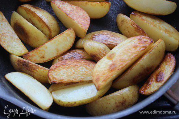 Картофель хорошо помыть, не чистить. Нарезать крупными дольками. Разогреть масло в сковороде и обжарить картофельные дольки на сильном огне до золотистой корочки. Переложить на тарелку.