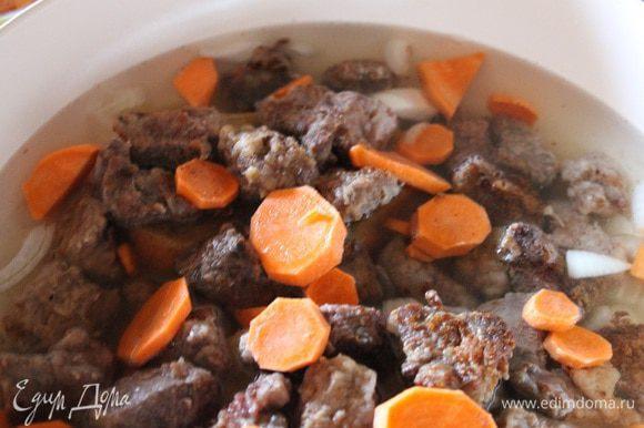 Заливаем водой так, чтобы мясо было покрыто полностью, сверху кладем нарезанную кружочками морковь. На сильном огне доводим до кипения, убавляем огонь до маленького,накрываем крышкой и тушим 1,5-2 часа. Периодически помешивая.