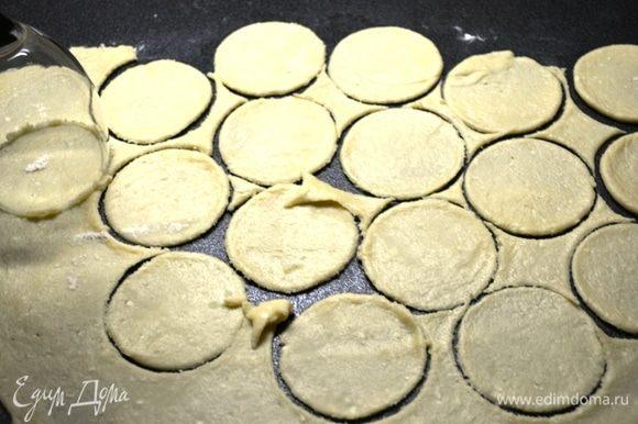 Из каждой части раскатываем круг толщиной 2-3 мм. Вырезаем на круге кружочки стаканом (диаметр меньше брать не стоит, поскольку готовое печенье будет суховатое).
